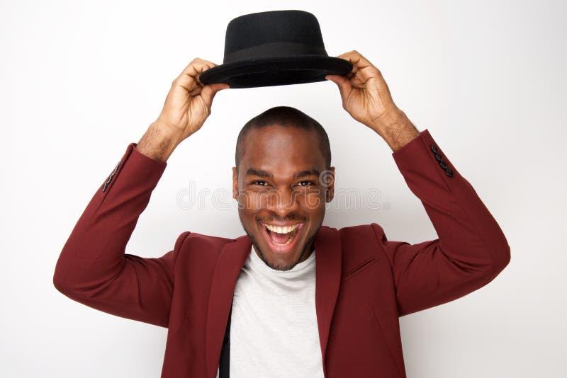 Chapéu afro-americano feliz da terra arrendada do homem acima da cabeça pelo fundo branco fotos de stock royalty free