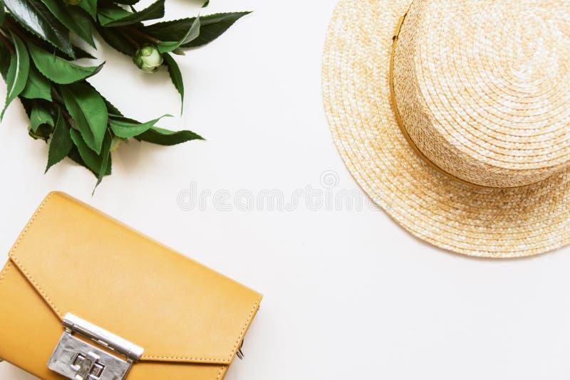 Chapéu amarelo do saco, da planta e de palha em um fundo bege foto de stock royalty free