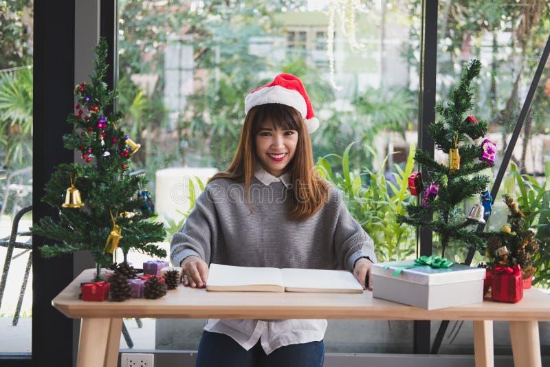 Chapéu asiático de Papai Noel do desgaste de mulher em casa menina com caderno, soldado imagem de stock royalty free