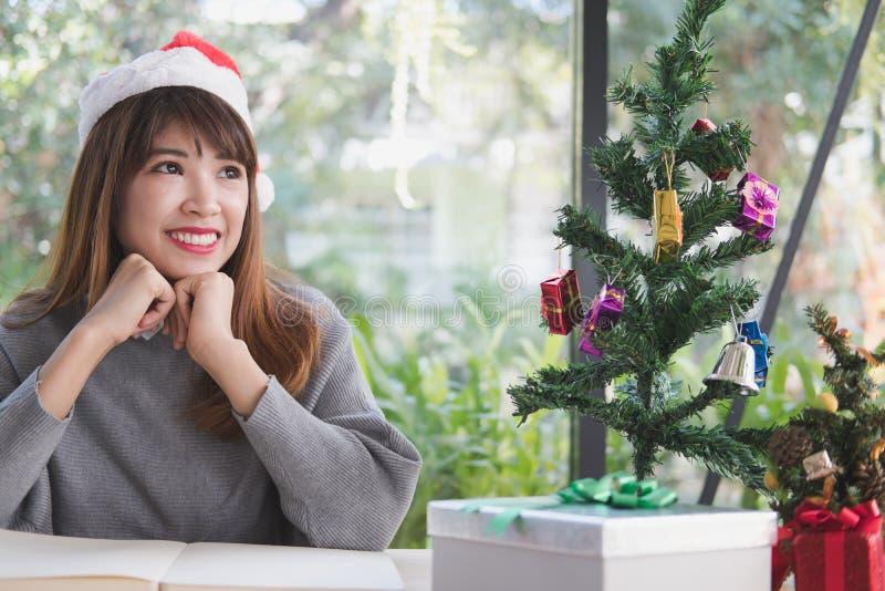 Chapéu asiático de Papai Noel do desgaste de mulher em casa menina com caderno, soldado fotografia de stock royalty free