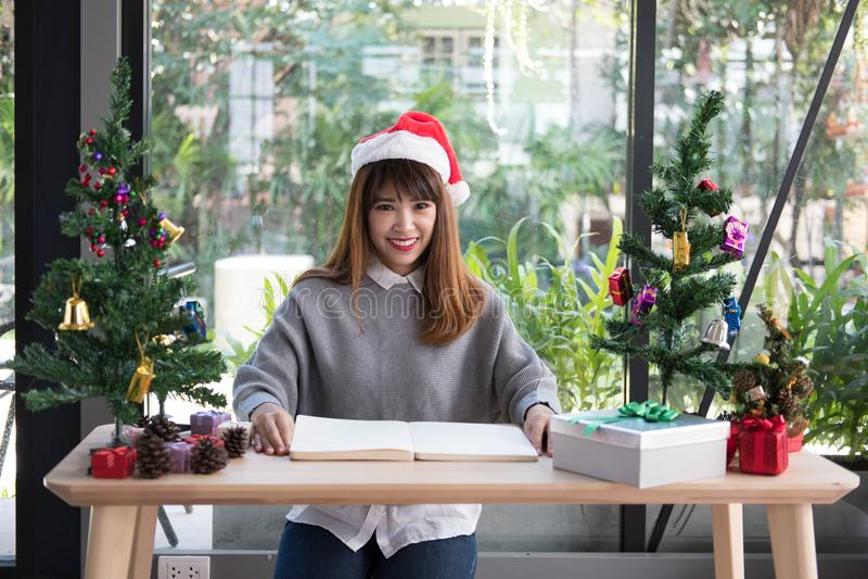 Chapéu asiático de Papai Noel do desgaste de mulher em casa menina com caderno, soldado imagens de stock royalty free