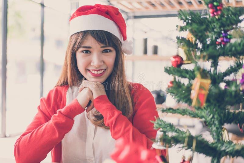 Chapéu asiático de Papai Noel do desgaste de mulher em casa menina com Natal tr fotografia de stock