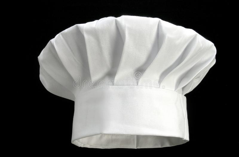 Chapéu branco dobrado do ` s do cozinheiro chefe em um fundo preto foto de stock