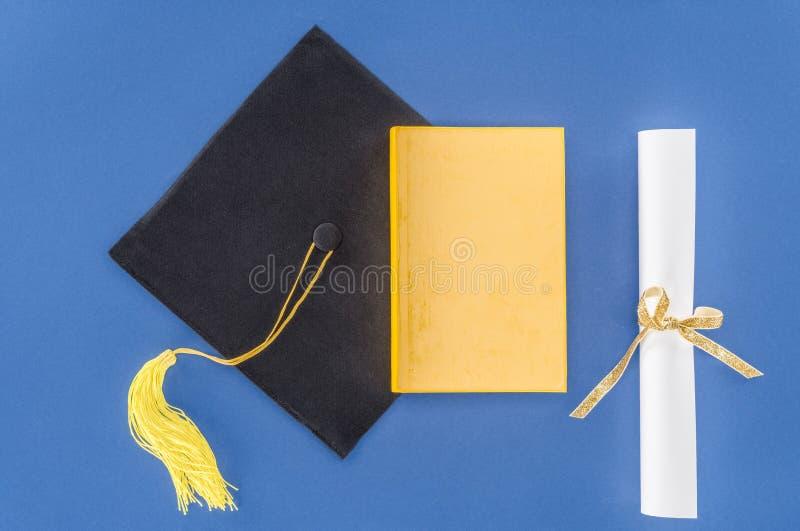 Chapéu da graduação com diploma e livro fotografia de stock