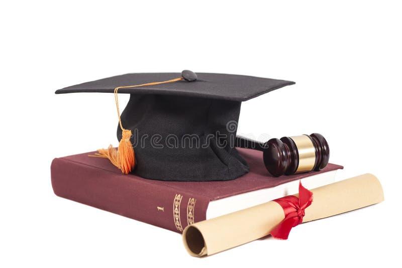Chapéu da graduação com o martelo do diploma, do juiz e o livro foto de stock