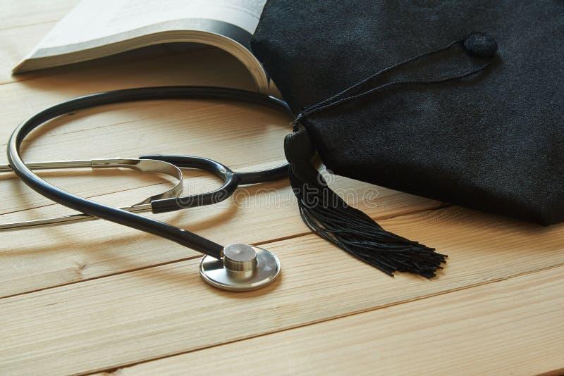 Chapéu da graduação em um livro aberto e em um estetoscópio preto no fundo de madeira fotos de stock royalty free