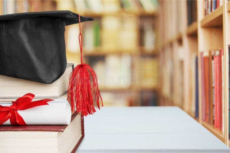 Chapéu da graduação na pilha de livros e de diploma foto de stock