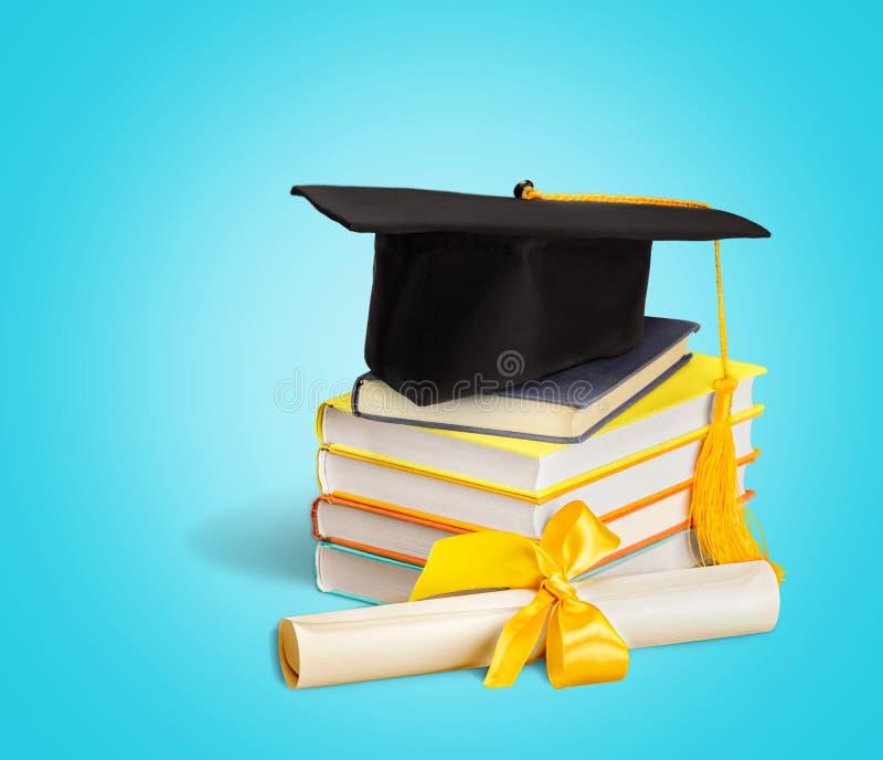 Chapéu da graduação na pilha de livros no azul fotos de stock royalty free