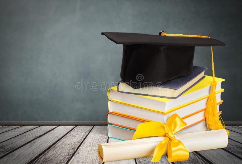Chapéu da graduação na pilha de livros na tabela de madeira fotografia de stock