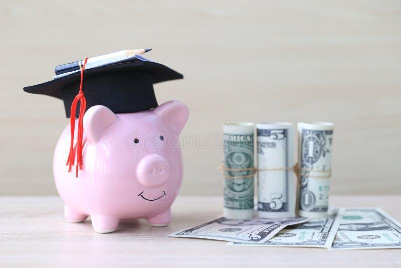 Chapéu da graduação no mealheiro cor-de-rosa com a cédula no fundo de madeira, dinheiro de salvamento para o conceito da educação imagem de stock