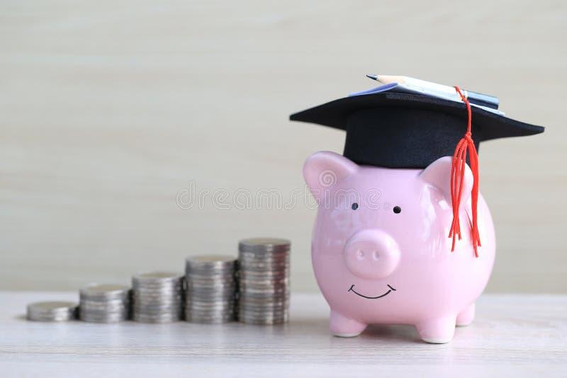Chapéu da graduação no mealheiro cor-de-rosa com a pilha de dinheiro das moedas no fundo de madeira, dinheiro de salvamento para  imagem de stock