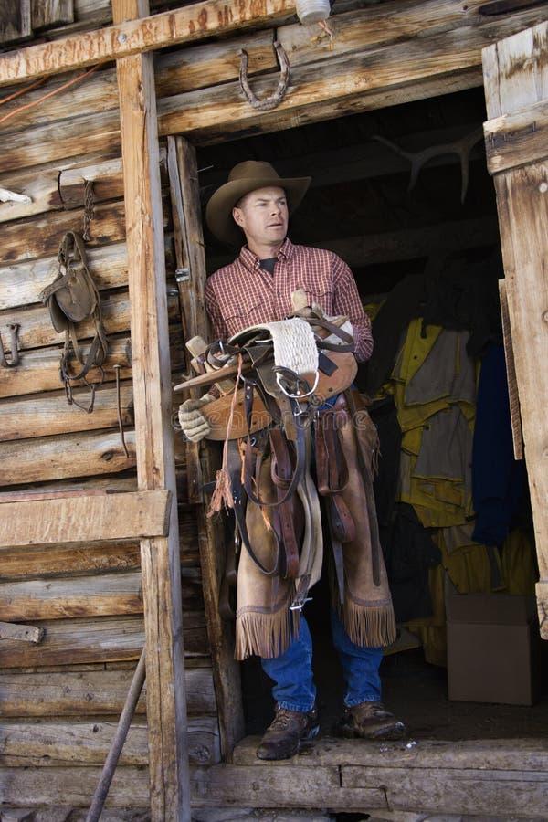 Chapéu de cowboy desgastando do homem que prende uma sela fotografia de stock