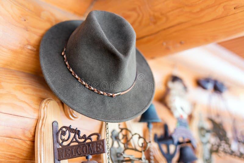 Chapéu de feltro clássico do vintage pendurado na parede Entrada da casa de madeira rústica Placa bem-vinda perto da porta Fundo  imagem de stock royalty free