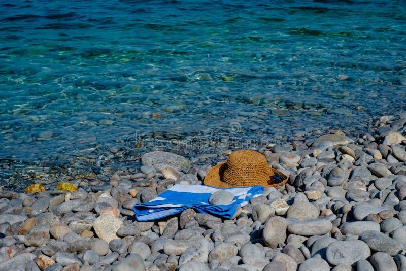 Chapéu de palha, óculos de sol, toalha em um seascape do fundo fotografia de stock royalty free