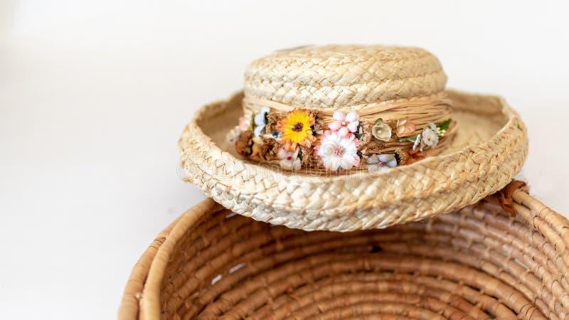 Chapéu de palha aparado em flores fritadas na cesta imagens de stock