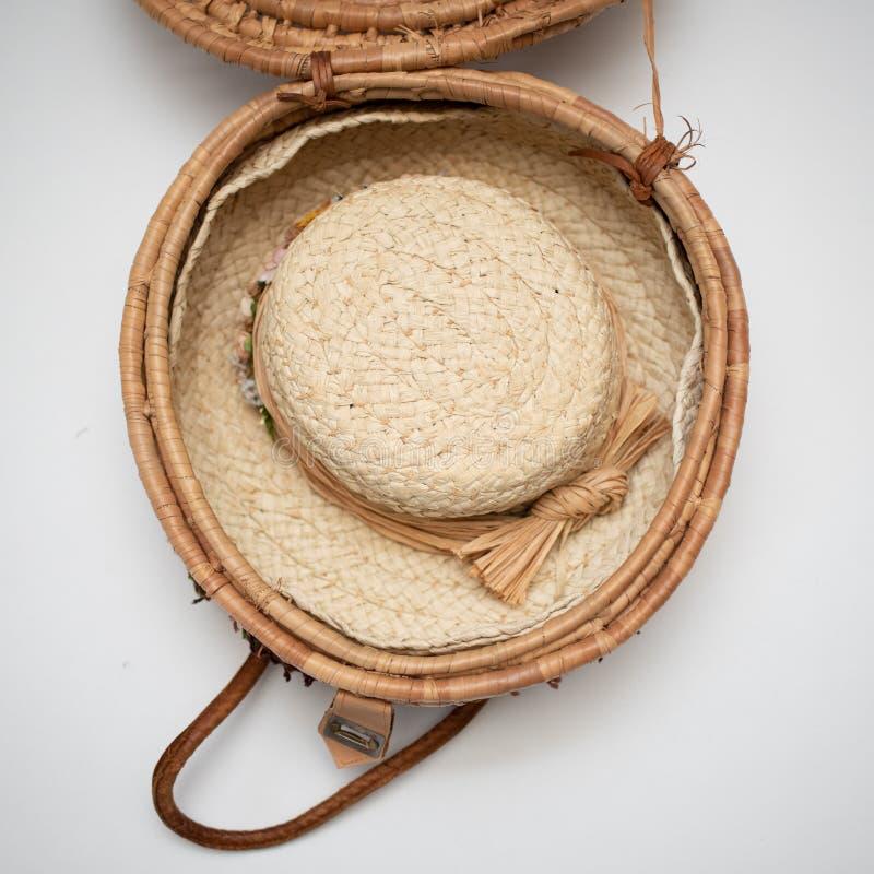 Chapéu de palha aparado em flores secadas para dentro da cesta tecida fotografia de stock royalty free