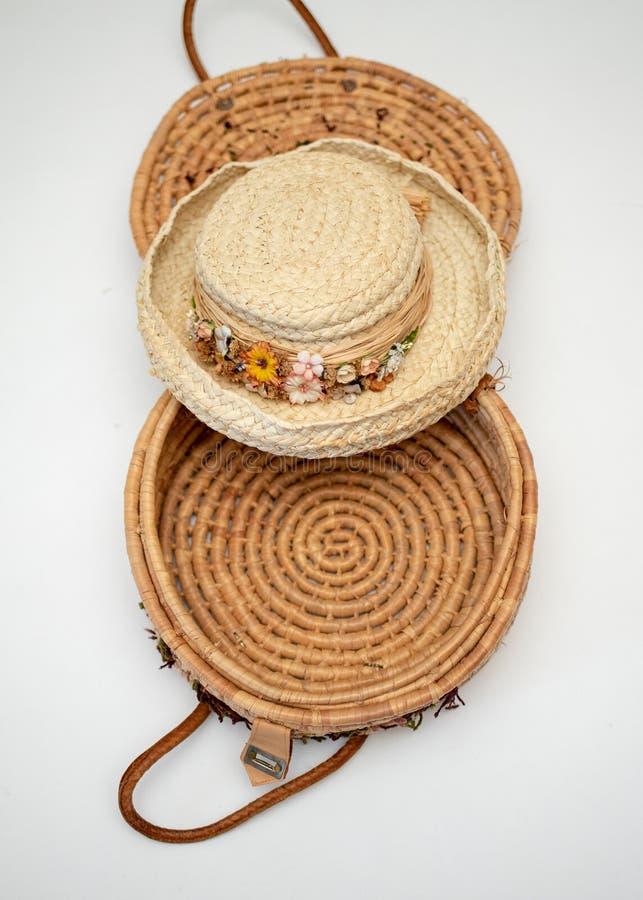 Chapéu de palha aparado em flores secadas sobre a cesta tecida imagem de stock