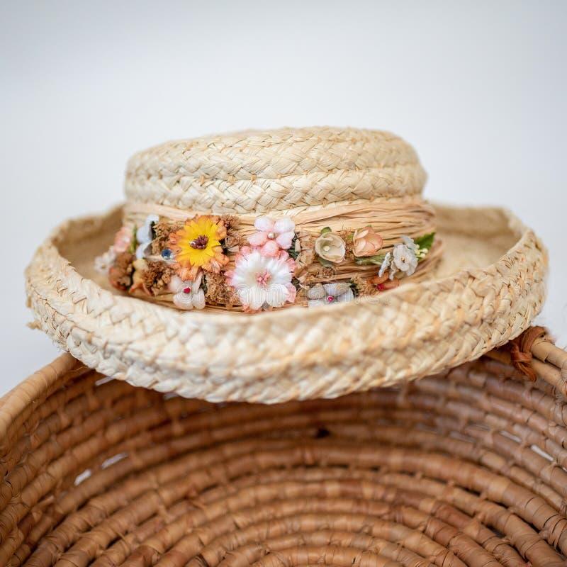 Chapéu de palha aparado em flores secadas sobre a cesta tecida foto de stock
