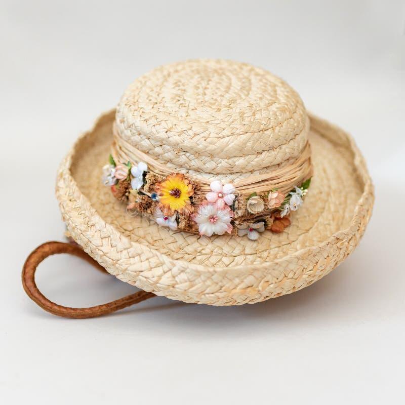 Chapéu de palha aparado floral da mola que senta-se sobre a cesta tecida feito a mão fotografia de stock royalty free
