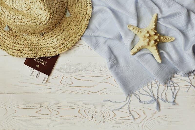 Chapéu de palha das mulheres, passaporte vermelho e bilhete plano, tippet azul e estrela do mar em um fundo de madeira branco - c fotografia de stock royalty free