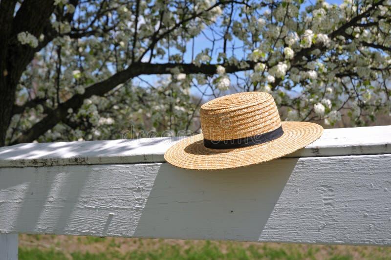 Chapéu de palha de Amish em uma cerca branca foto de stock