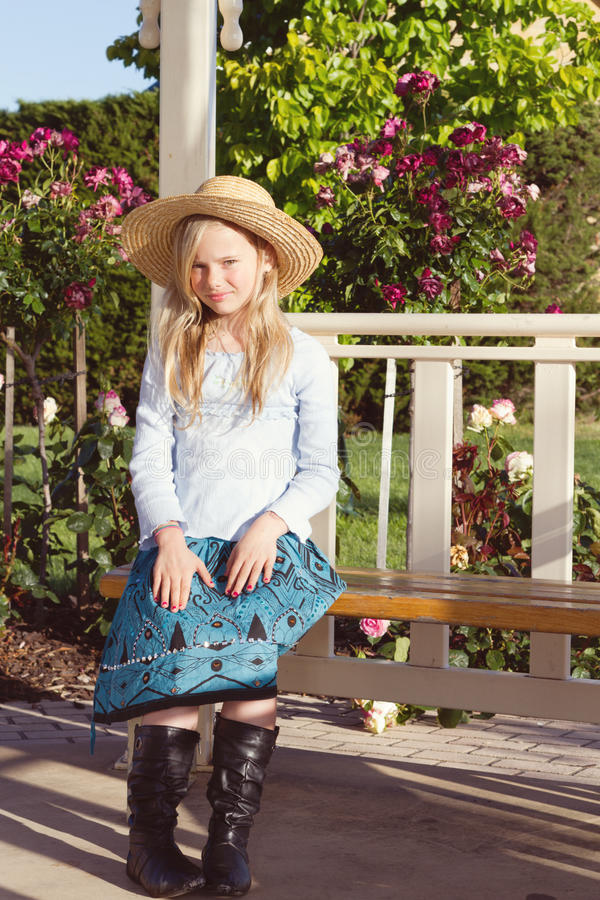 Chapéu de palha desgastando da menina no jardim foto de stock