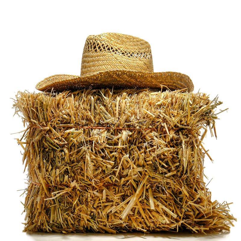 Chapéu de palha do fazendeiro do cowboy na bala de feno sobre o branco foto de stock