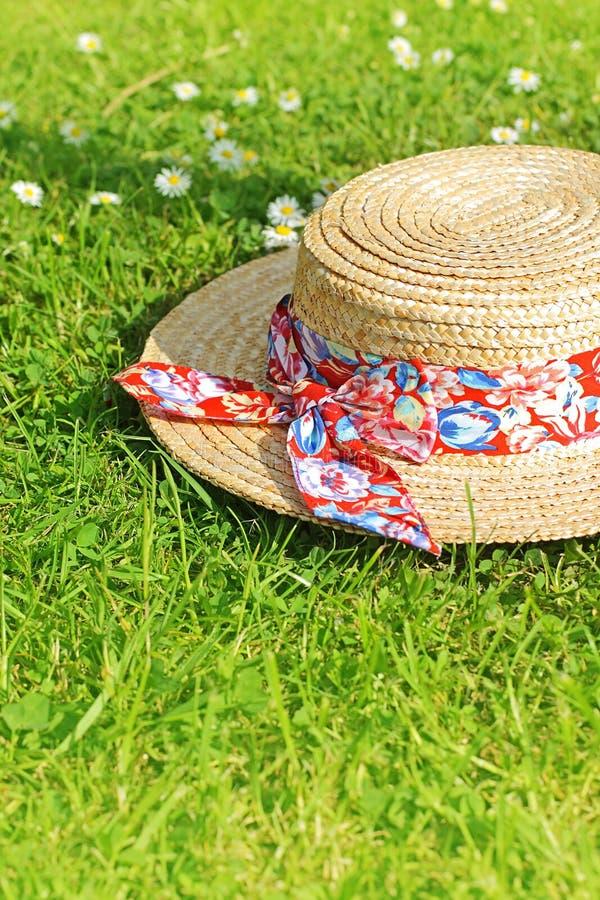 Chapéu de palha do verão na grama fotos de stock royalty free