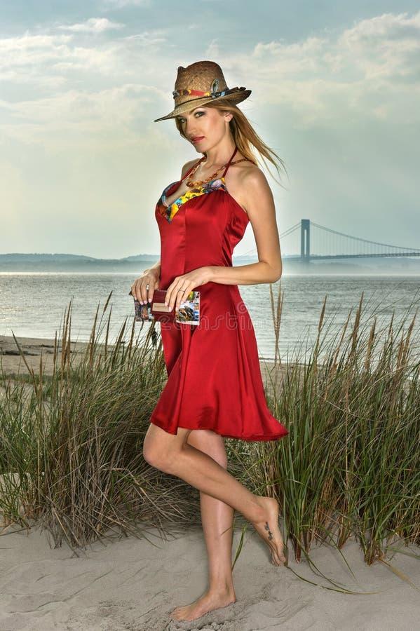 Chapéu de palha vestindo da mulher loura 'sexy' bonita nova e vestido vermelho elegante que levantam na praia fotos de stock