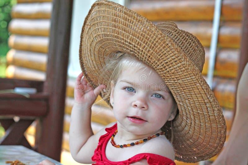 Chapéu de palha vestindo do bebê imagem de stock