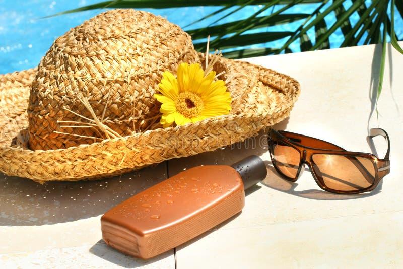 Chapéu de palha, vidros e loção do suntan fotografia de stock