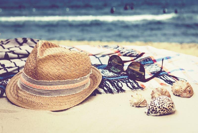 Chapéu de palha, vidros de sol e envoltório do roupa de banho do encobrimento em uma praia tropical com escudos do mar imagens de stock royalty free