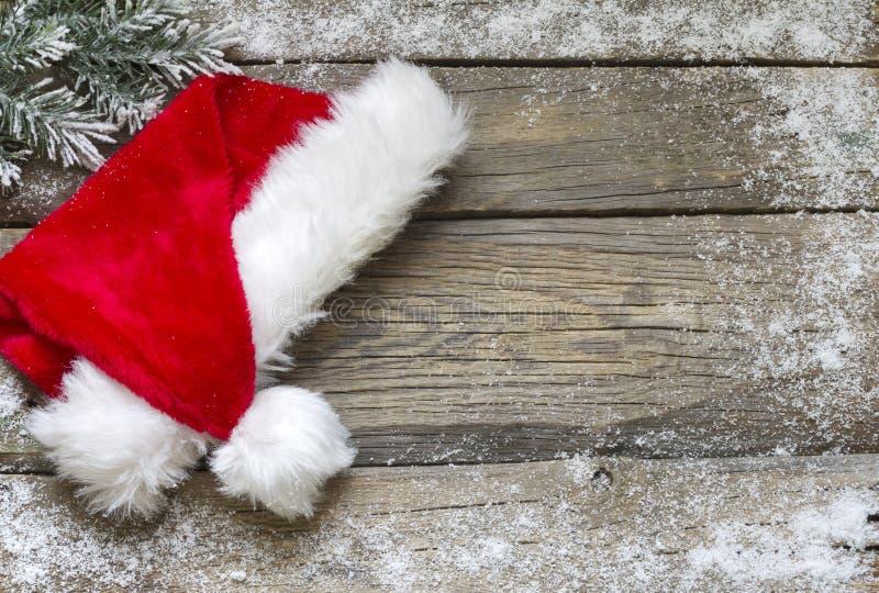 Chapéu de Santa Claus no fundo do Natal das placas de madeira do vintage imagens de stock royalty free