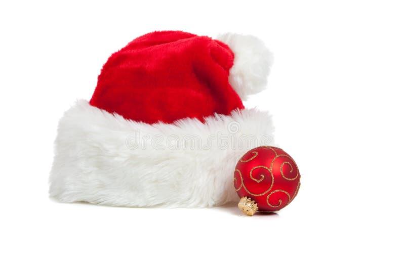 Chapéu de Santa e uma esfera do Natal no branco imagens de stock