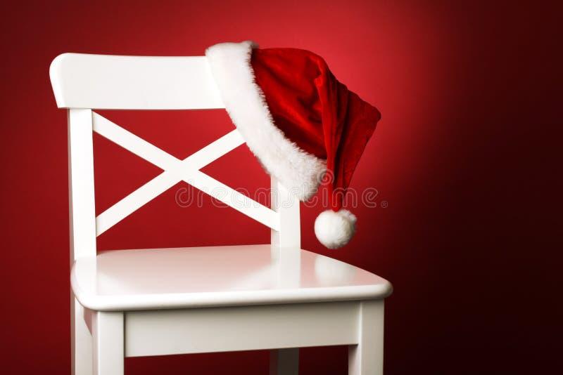 Chapéu de Santa na parte dianteira branca da cadeira do fundo vermelho fotos de stock