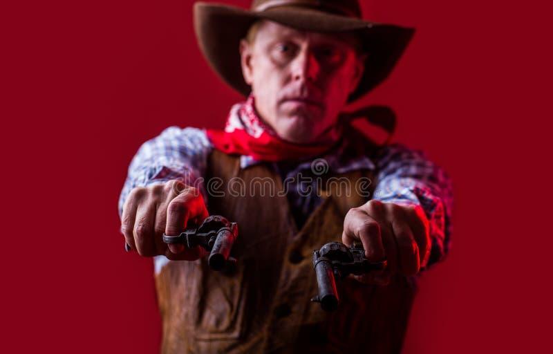 Chapéu de vaqueiro vestindo do homem, arma Retrato de um vaqueiro Oeste, armas Retrato de um vaqueiro Bandido americano na máscar foto de stock royalty free