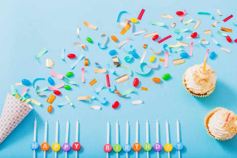 chapéu do aniversário com confetes e queque no fundo azul imagem de stock royalty free