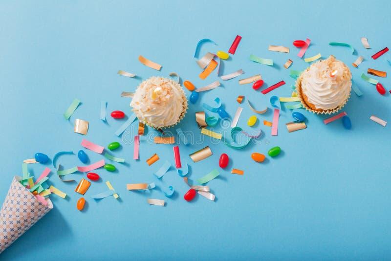 Chapéu do aniversário com confetes e queque no fundo do papel imagens de stock