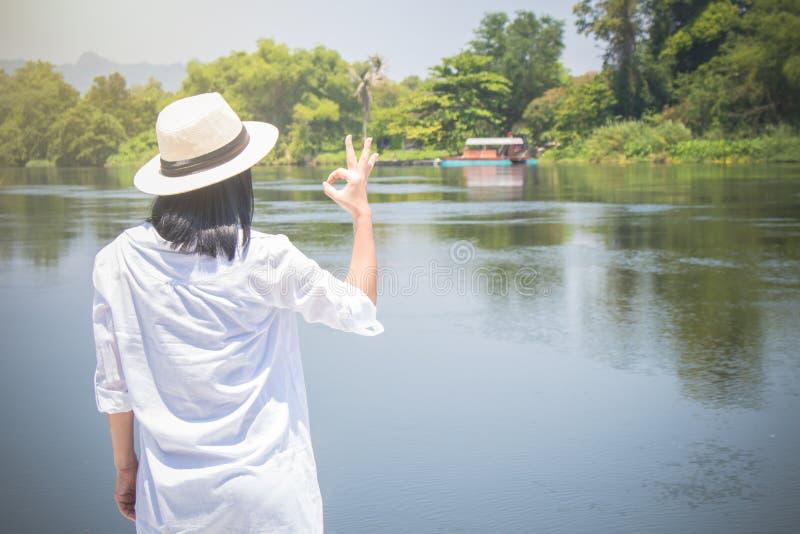 Chap?u do desgaste de mulher e a camisa branca com posi??o na ponte de madeira, que olha para a frente ao rio com faz o gesto da  fotos de stock royalty free