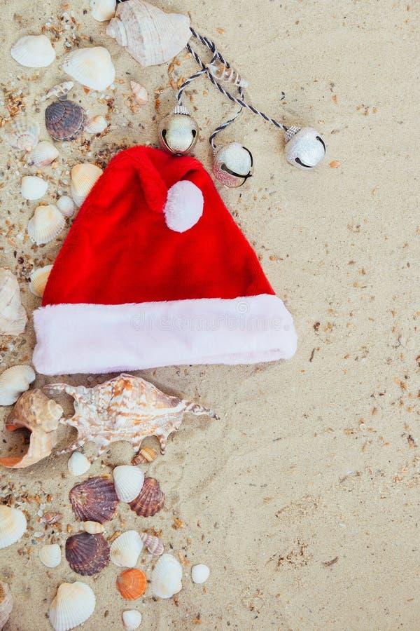 Chapéu do Natal na praia Santa a areia perto dos shell feriado Férias do ano novo Copie o espaço Quadro Vista superior fotografia de stock
