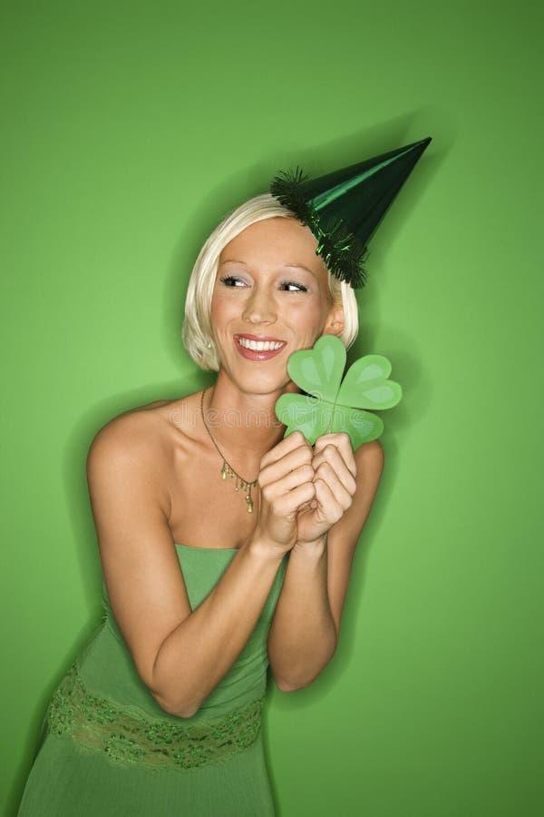 Chapéu do partido da mulher caucasiano nova e shamrock desgastando prender. foto de stock royalty free