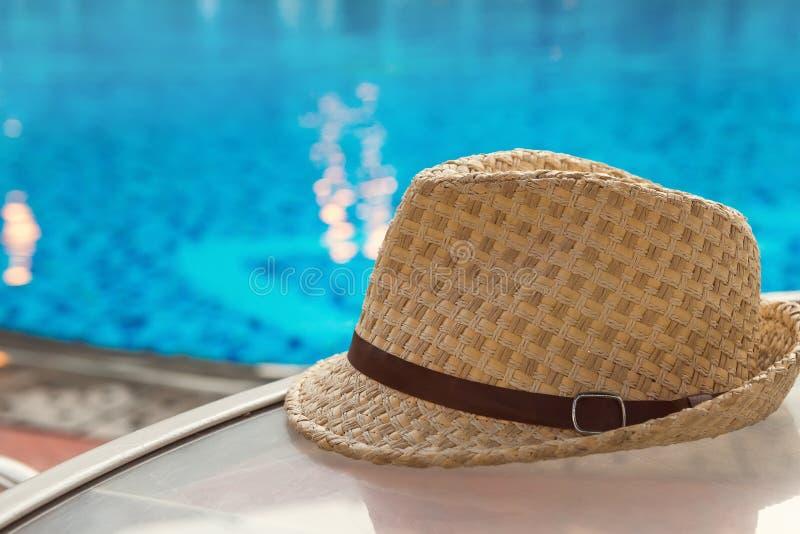 Chapéu do verão na tabela perto da associação azul brilhante, espaço da cópia, foco seletivo Férias e conceito das férias de verã imagens de stock royalty free