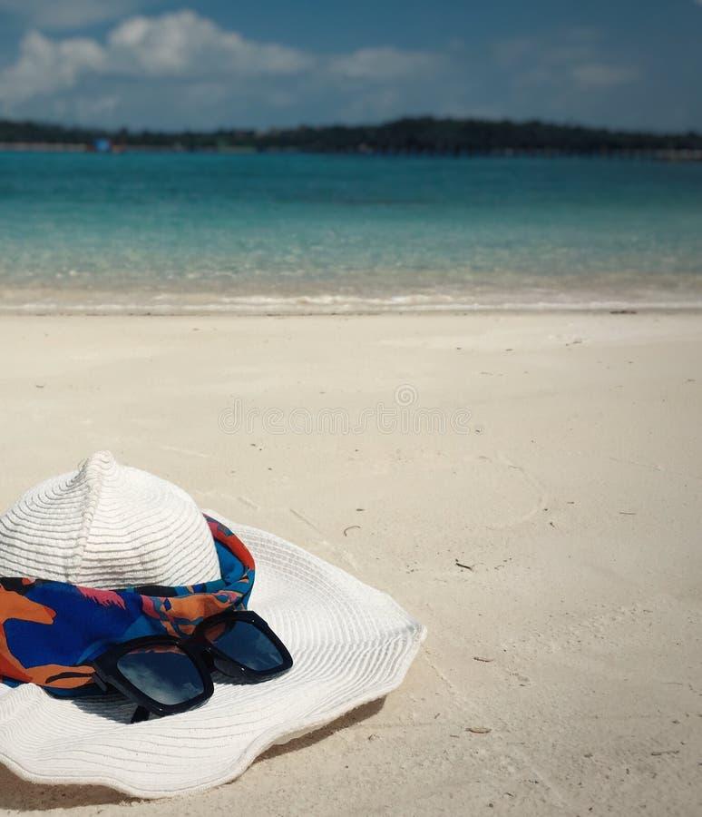 Chapéu e óculos de sol brancos em uma praia fotos de stock royalty free