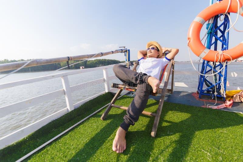 Chapéu e óculos de sol do desgaste de homem Encontra-se em sunbeds no navio de cruzeiros foto de stock royalty free