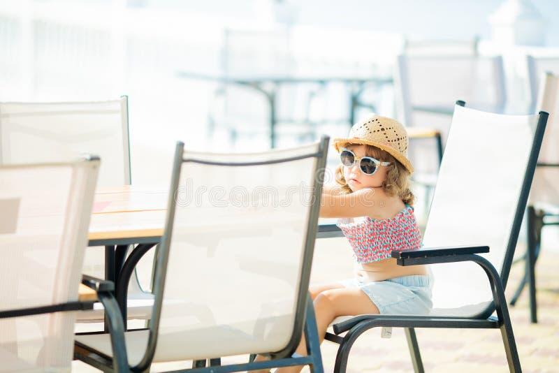 Chapéu e óculos de sol vestindo de palha da menina pequena do turista que sentam-se no restaurante do ar livre, mar no fundo imagem de stock