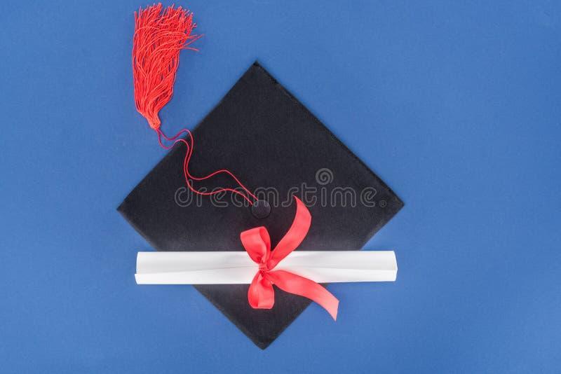Chapéu e diploma da graduação com fita vermelha imagem de stock