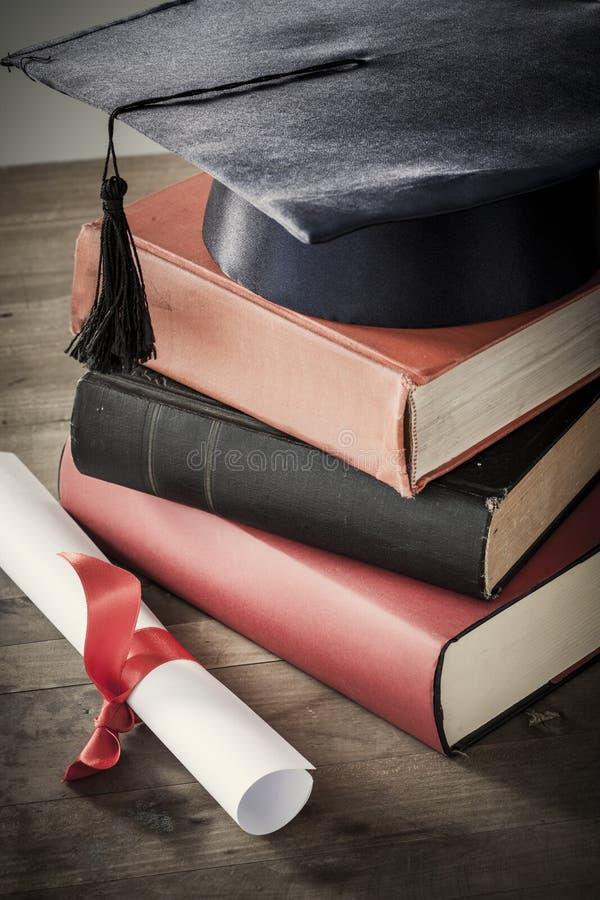 Chapéu e diploma da graduação com o livro na tabela imagens de stock royalty free