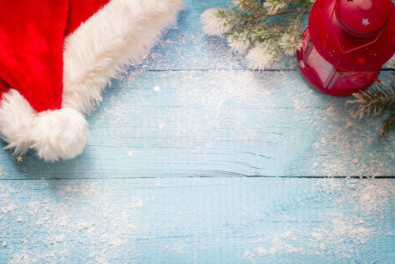 Chapéu e lanterna de Santa Claus no sumário nevado azul das placas foto de stock