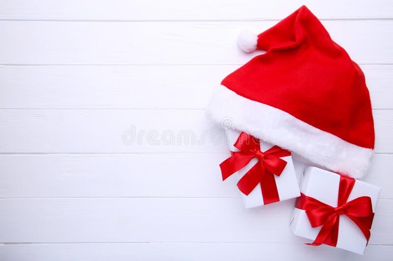 Chapéu e presentes vermelhos de Santa Claus no fundo branco imagem de stock royalty free