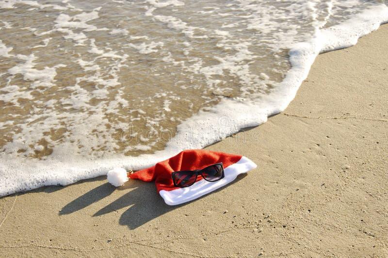 Chapéu e sunglass de Santa na areia do thr. foto de stock royalty free
